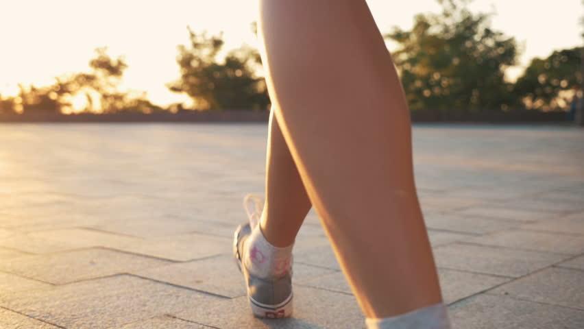 Close up shot of feminine feets walking in park during sunset or sunrise