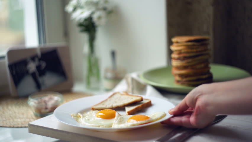 Fried eggs and slices of toast bread on white plate. Woman put morning breakfast on plate on kitchen table