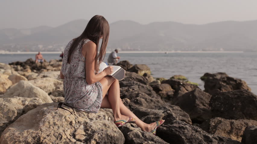Yong woman making notes in diary on the beach | Shutterstock HD Video #18544124