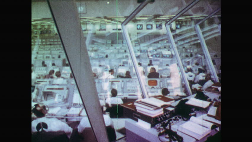 UNITED STATES 1960s:View of People Working at Stations as they Wait for Space Rocket to Launch. Sun Rising Behind a Hill. People Sat on Floor Watching Camels. | Shutterstock HD Video #18554414