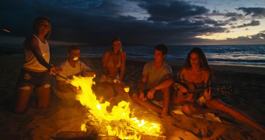 4k0026Friends Roasting Marshmallows Over Bonfire On The Beach At Sunset