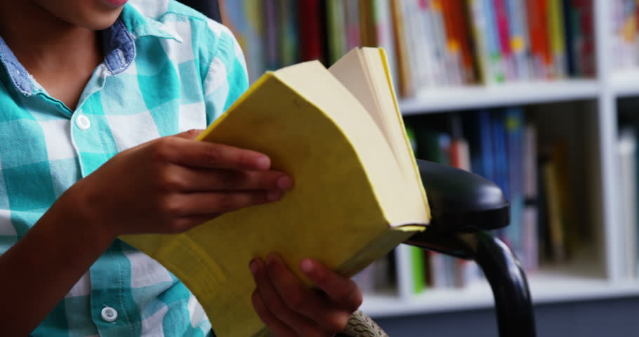 Slow motion of disabled school boy reading book in library at school 4k