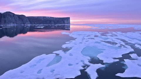 Drifting past sea ice under the midnight sun on Scott Island off Baffin Island in Nunavut, Canada. (Nunavut, Canada 2010s)