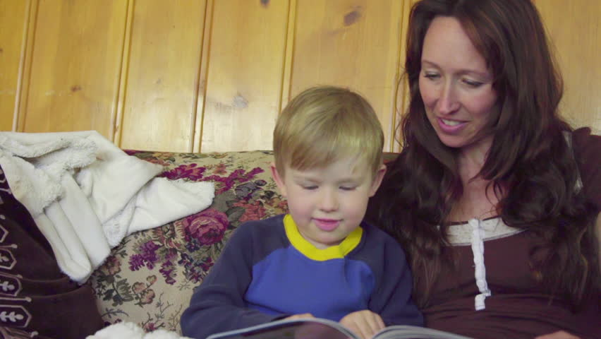 A mother sits on a couch with her boy and reads a book with her son