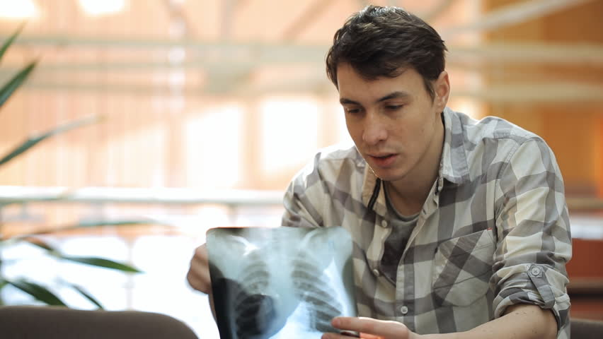Young man attentively looks at roentgenogram of lungs. | Shutterstock HD Video #18768824