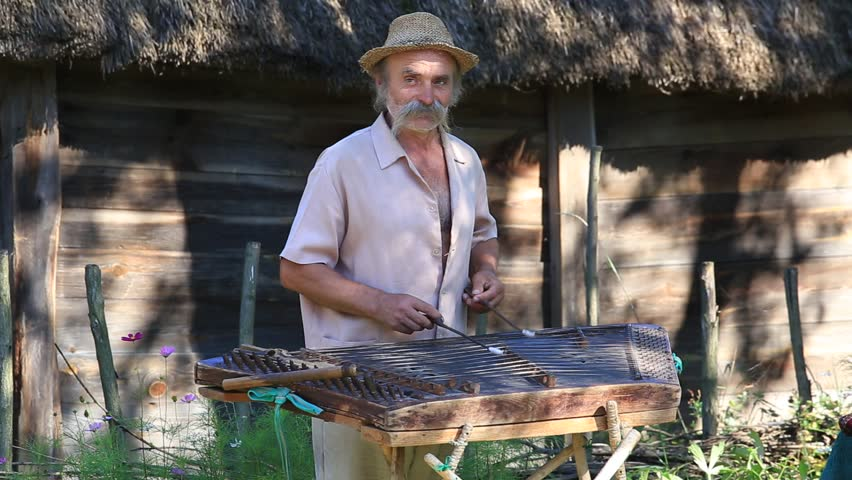 KIEV, UKRAINE - AUGUST 6, 2016 :Unknown old Ukrainian musician playing the national stringed musical instrument gusli in ethnic village Pirogovo, Kiev, Ukraine | Shutterstock HD Video #18772814