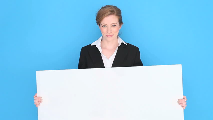 Happy smiling businesswoman holding a blank white sign tilted slightly , studio portrait on blue