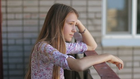 Unhappy teenager girl at home balcony terrace. Teen Depression