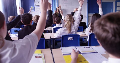 4k, A group of school children raising their hands in class. Slow motion.