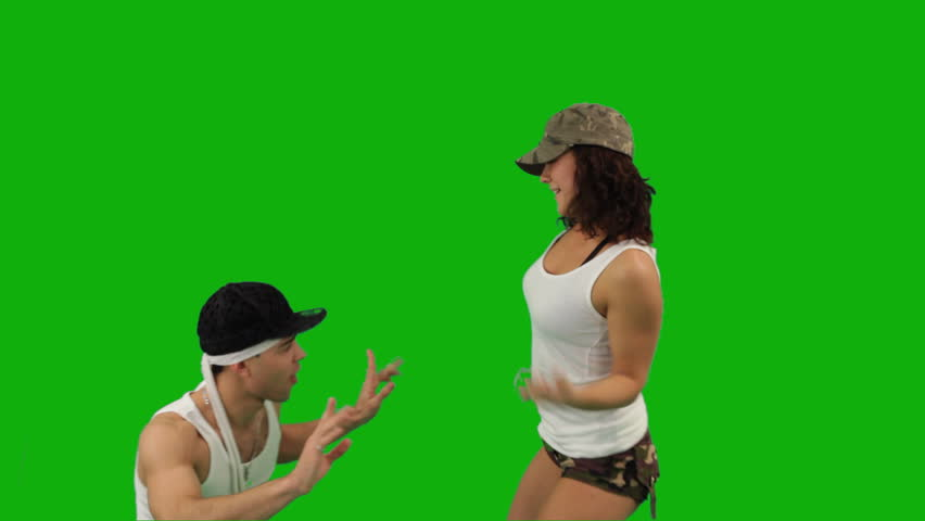 A girl and a guy dressed in military-style clothes dancing hip-hop battle.