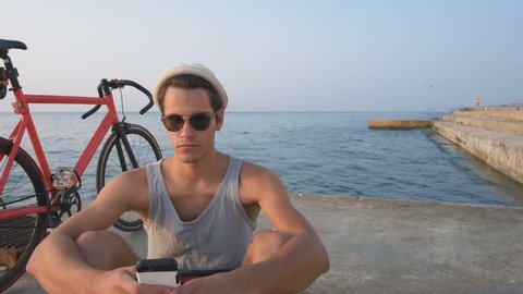 Young hipster man with his fixed gear bike using smart phone near the sea