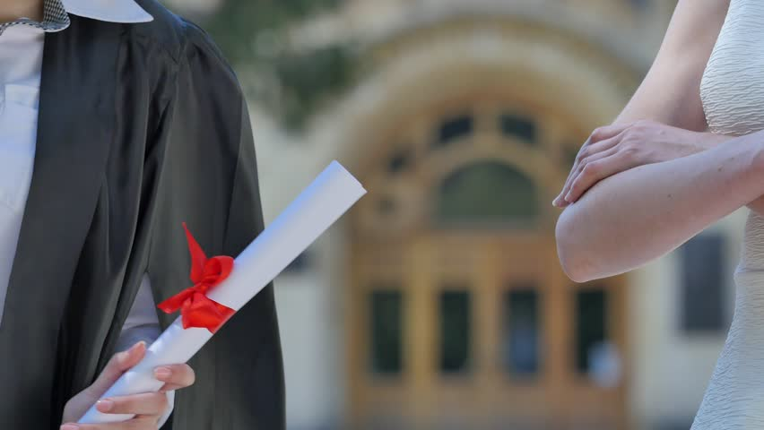 Graduand Gets the Diploma, Women's Hands Close Up. Shaking Hands. Teacher Gives a Paper. Young Woman in Student Mantle is Holding Rolled up Diploma Tied up With Red Tape and Shakes the Paper. Student | Shutterstock HD Video #18902075