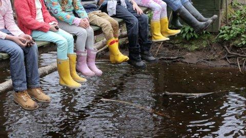 Close Up Of Children's Feet Dangling From Wooden Bridge