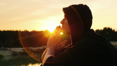 Young man praying at sunset. He sits in profile to the camera hood, clasped his hands together in prayer