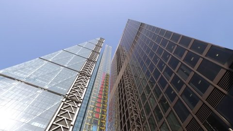 Moving underneath the tall cheese grater building in London past other high rise glass office buildings.