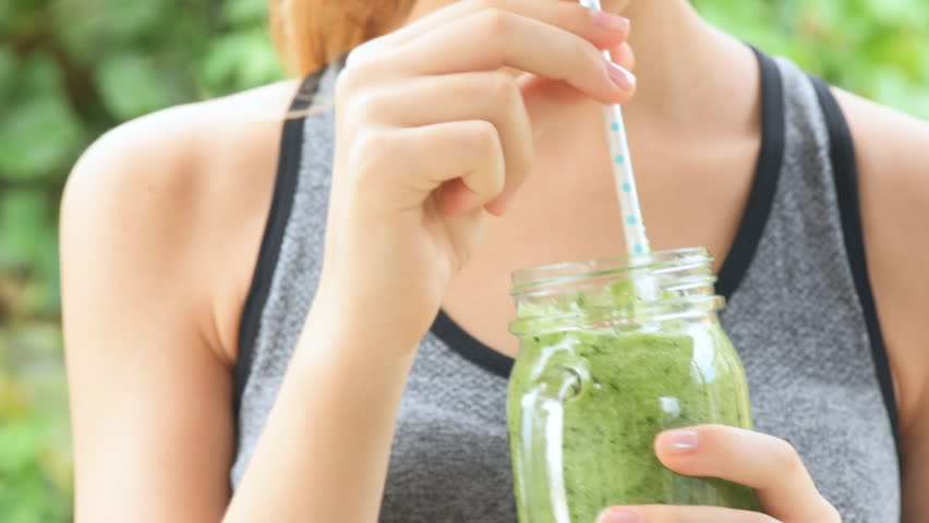 Young girl drinking fruit smoothie . Fitness and healthy lifestyle concept.