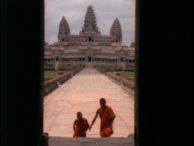 Buddhist monks walk up the stairs of Angkor Wat.