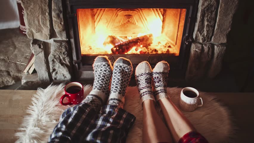 Couple Feet in Woollen Socks by the Cozy Fireplace, 4K. Man and Woman relax by warm fire and warming up their feet. Close up. Winter and Christmas holidays concept.  | Shutterstock HD Video #18943325