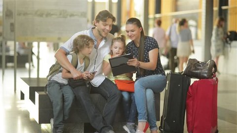 Members of a big family are watching photos from the vacation in tablet PC while sitting in waiting room of airport or railway station.