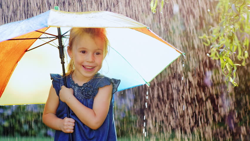 Carefree girl three years under the umbrella of color. Hiding from the rain