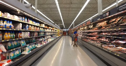 MONTREAL, CANADA - AUGUST 2016: Shopping Inside Walmart - Professional Steadicam Shot (Refrigerated Dairy Products & Meats - Milk, Chicken, Beef, Bacon & Orange Juice)