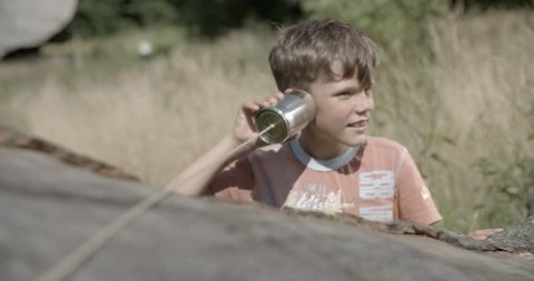 Boy talks in a tin can phone and listens to it