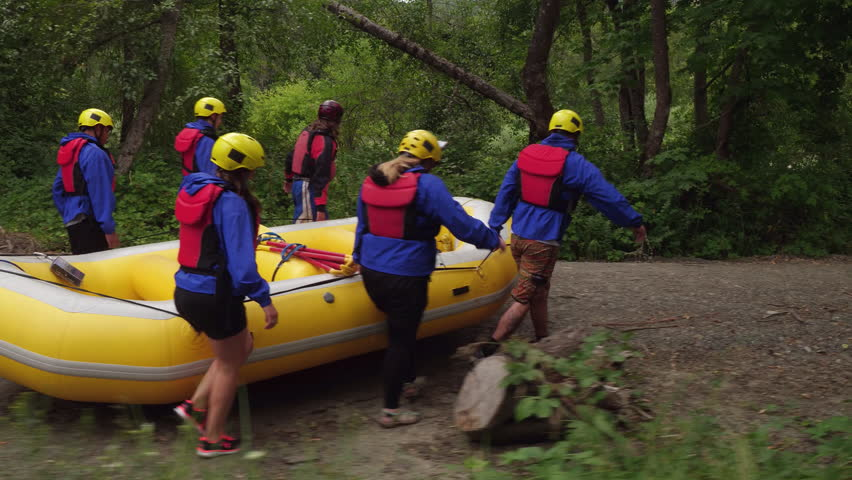 Group of people white water rafting carry raft together