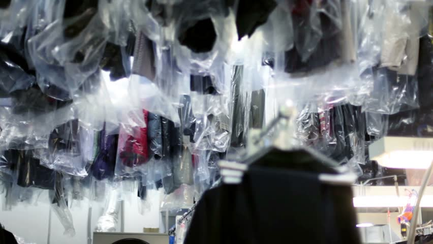 Many clothes in polyethylene slipcovers hang and move in dry cleaning