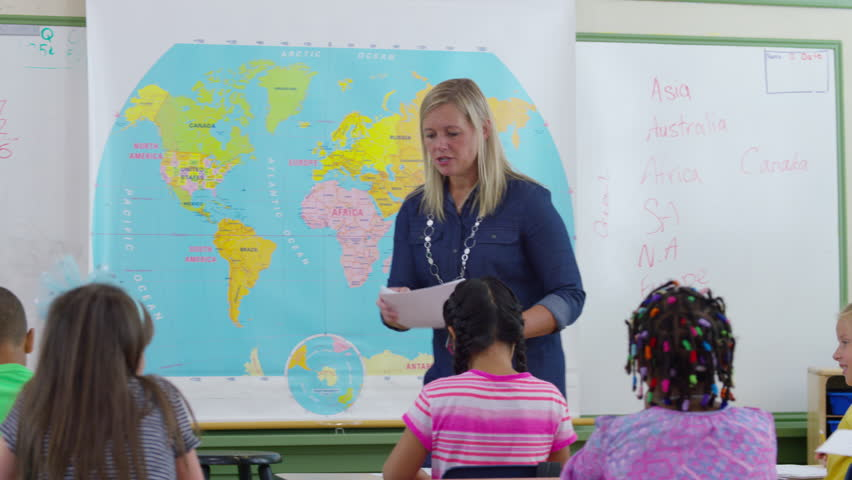 Young teacher using interactive whiteboard to display the world teacher passing out papers in school classroom 4k stock video clip gumiabroncs Gallery