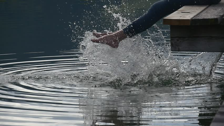 Woman feet dipped into the lake splash water into big wave and lots of shining drops, slow motion