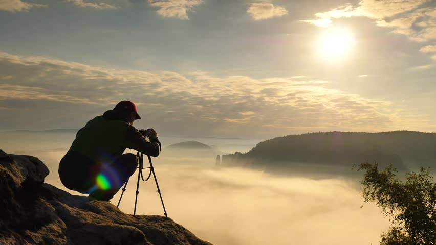 Photographer in green windcheater and black trekking trousers stay camera on tripod at cliff edge. Dreamy fogy landscape, blue misty sunrise in a beautiful valley below | Shutterstock HD Video #19012504