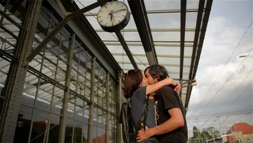 Happy couple embracing on railway station platform. Farewell at the train station, young girl and guy kissing on platform
