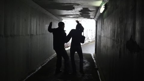 Silhouette of a man attacks  a young woman with a knife in a dark tunnel. Violence against women concept. Real people, copy space