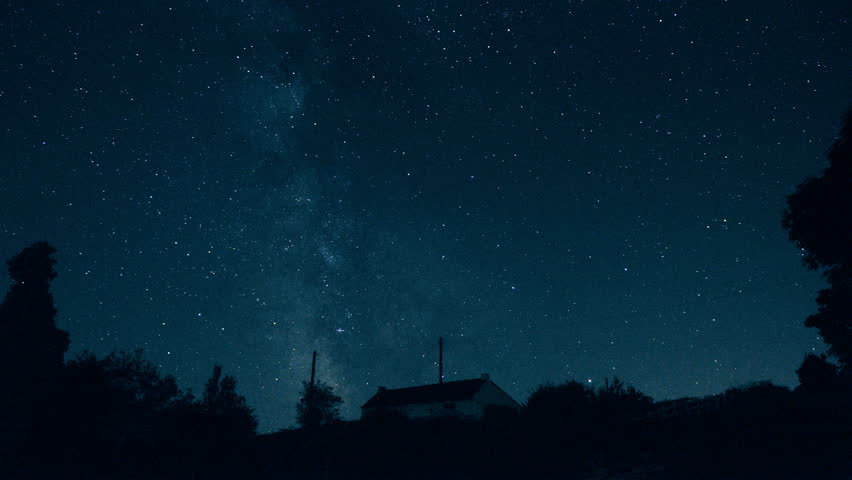 "Stars and the Milky Way moving in the sky - Starry night sky in timelapse - ISS flashes at 2""17 (top center) - Looking to southwest from western Europe above an isolated house in countryside."