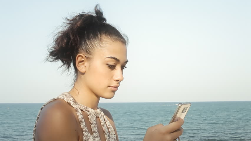 A pretty girl looking at her smartphone, disappointed by what she's reading. Sunny day, near the sea. Close-up shot.