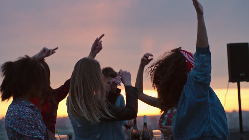 Group of young multi-ethnic people dancing energetically to the music played by dj at rooftop party at sunset