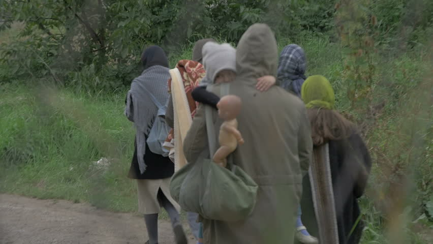 Man with  hood holding little female child who drop down  baby doll while they walking with rest of family on the muddy road in slow motion,tilt down,concept refugees, poverty,homeless,symbolic video.