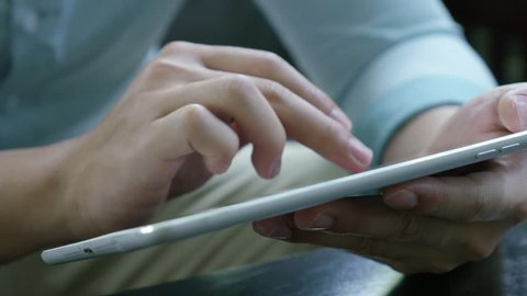4K : Asian young man sitting on a sofa and using tablet pc