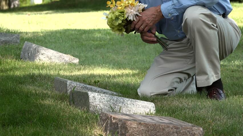 Man placing flowers on a grave, medium shot