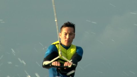 Close up shot asian man in diving suit wake boarding behind the speed boat in cold water on sunset