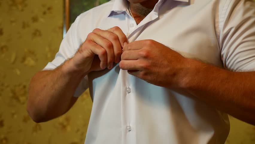 man in a white shirt putting on a tie video