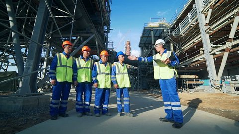 Industrial engineer and workers discussing in factory
