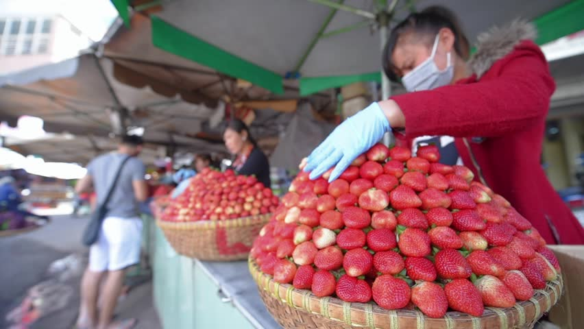 DA LAT, VIETNAM - AUGUST 6, 2016: Unidentified, woman sitting at the market selling fruits Da Lat, this is the largest market in Da Lat