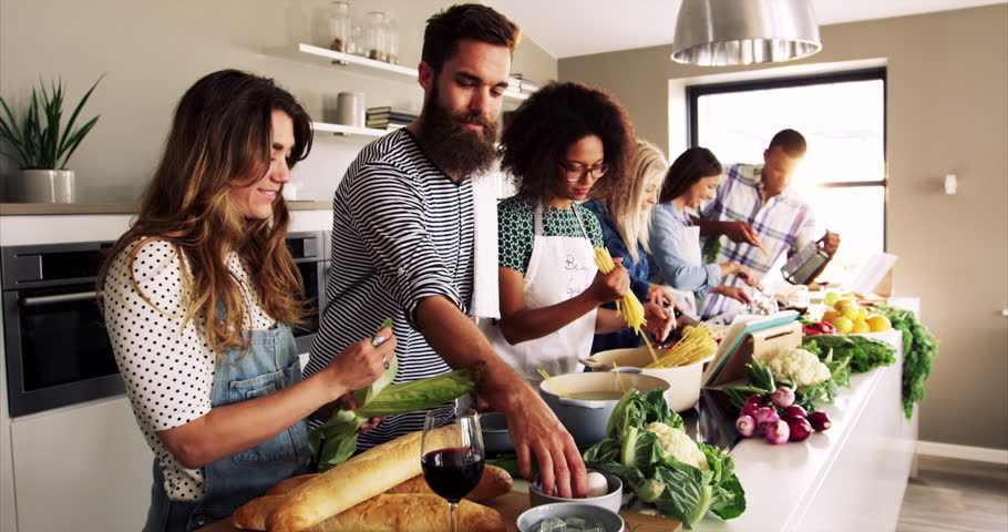 A Group of friends preparing dinner in a kitchen cooking and frying on pots and pans, concept of teamwork and good releations