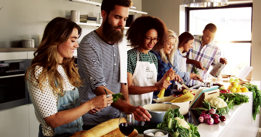 A Group of friends preparing dinner in a kitchen cooking and frying on pots and pans, concept of teamwork and good releations | Shutterstock HD Video #19230436