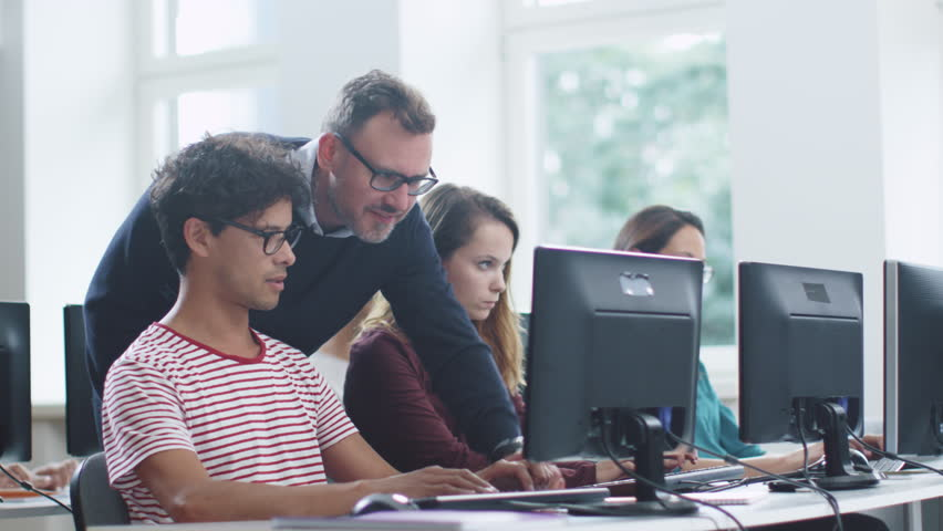 Teacher Talking with Students and Helping them in Computer Class. Shot on RED Cinema Camera in 4K (UHD). | Shutterstock HD Video #19294786