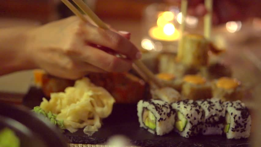 Happy couple eating sushi rolls in japan restaurant, sushi bar. Dinner. People eating Japanese food, diet, dieting. Slow motion 240 fps, high speed camera shot. Full HD 1080p