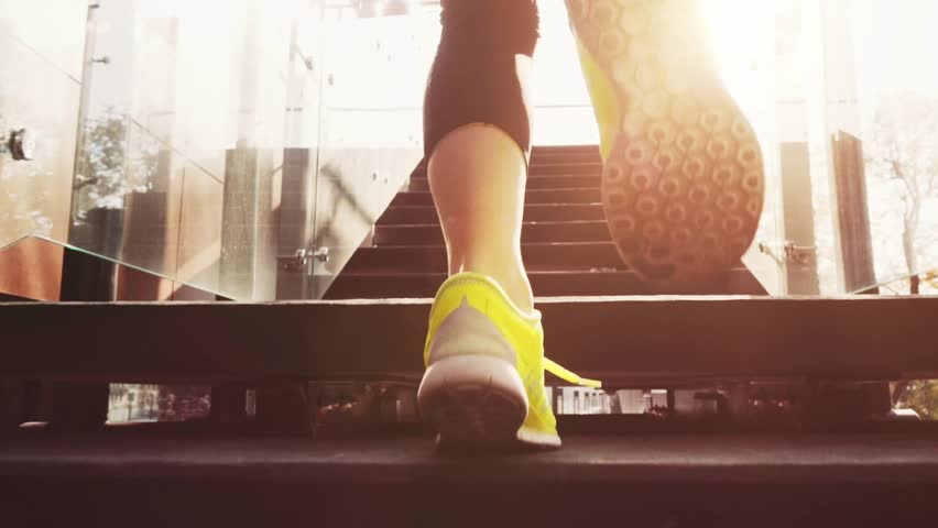 Runner Woman Feet Jogging up Stairs, Close Up, Lens Flare. SLOW MOTION 120 fps Steadicam STABILIZED shot. Athletic Healthy Female in Bearfoot Sports Shoes Running Up the Modern Sunny Glass Stairs.
