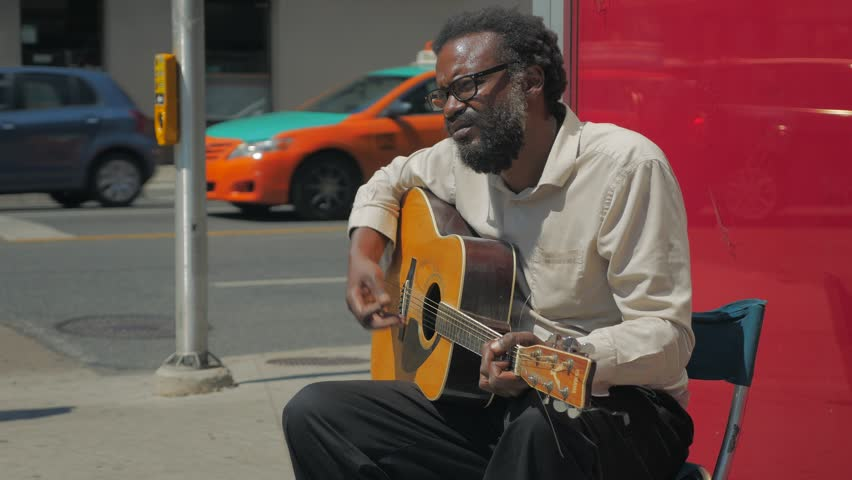 Toronto, Canada - CIRCA: August, 2016: Close up of black male with a beard busking by sitting and playing a guitar on a sidewalk in front of a bank while pedestrians walk by