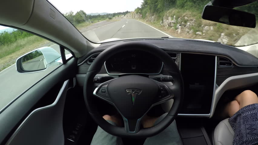CRNI KAL, SLOVENIA - JULY 20: Self driving electric car using sensors and navigating without driver on winding coastal road. Unrecognizable person steering autonomous car fast with no hands on wheel